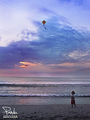 Child flying a simple Diamond kite at the beach.