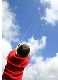 A boy flying a purple 2 line Diamond on a cloudy day.