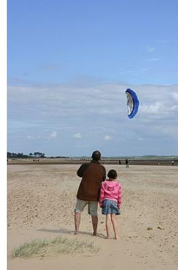 A man flying a small dual line power kite down at the beach.