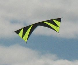 A black and flouro green quad kite in flight.