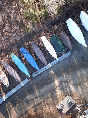 An artistic example of kite photography, featuring upturned hulls of boats and tree shadows