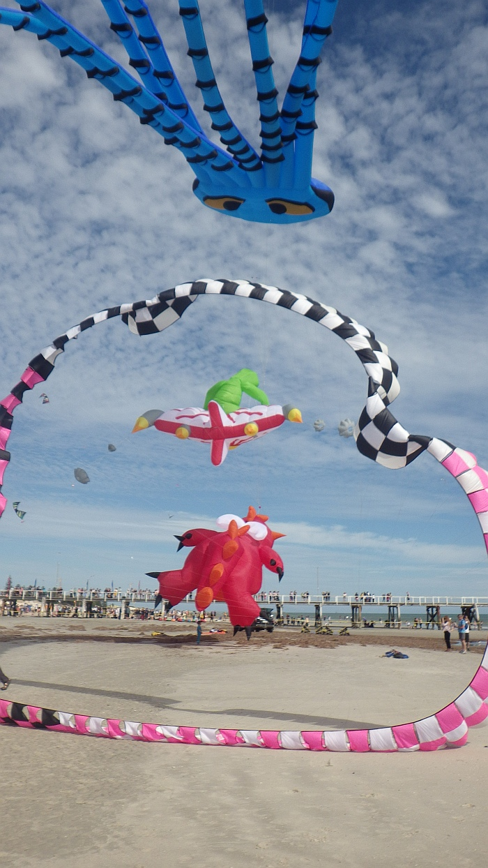 AIKF 2017. A worm-like circular 'kite' frames a Surfing Alien and a Dragon inflatable.