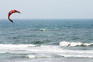 Restraining a large kite with one arm, while dragging the other in the water
