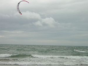 A speeding kite surfer obscured by his own spray.