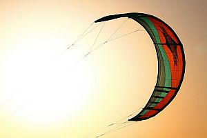 Great into-sun shot of a surfing kite, taken near sundown.