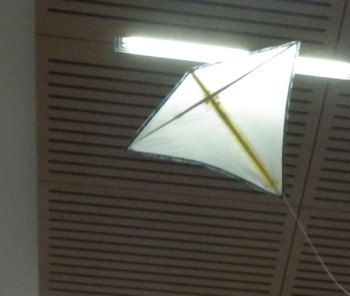 The MBK Indoor Diamond kite flying under a high roof.