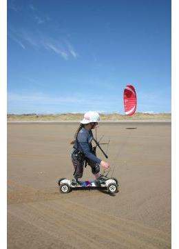 Lady kite boarding across an ideal dry surface.