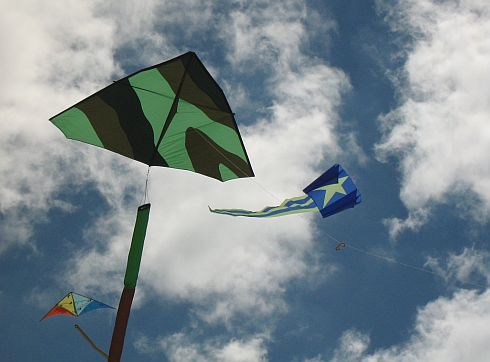 A large green Delta and a blue Sled over Semaphore Beach
