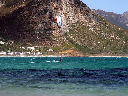 Kite surfing against a mountainous backdrop.