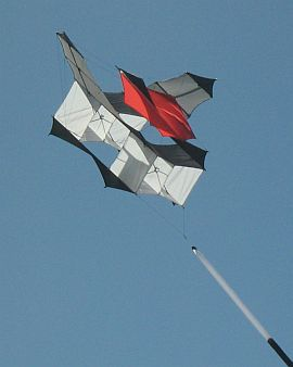 A light-wind Cody kite with red top sail.