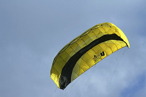 A four-line yellow and black parafoil kite in flight.