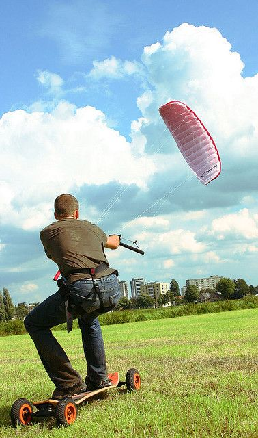 Power kite pulling a land board rider over grass.