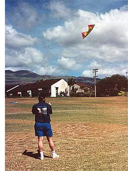 This man is flying a colorful quad kite in a grassy vacant block.