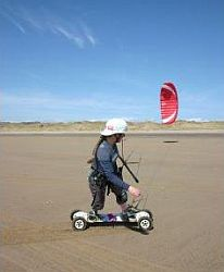 Kite landboarding along, over a smooth dirt surface.