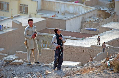 Kite runners in Afghanistan. Some boys waiting for a kite to fall.