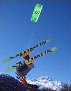 A skier getting air under a large snow kite.